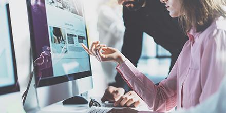 Photo de collègues de travail devant un ordinateur dans un bureau.