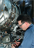 Photo of a technician repairing an aircraft engine