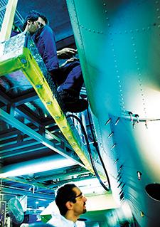 Photo générique : Deux techniciens travaillant sur une carlingue d'avion width=