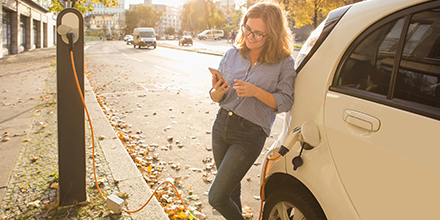 Young woman is standing near the electric car and looks at the smart phone. The car is charging at the charging station for electric vehicles.Shutterstock.