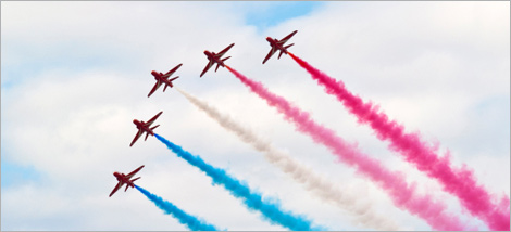 Photo of an air show: five planes releasing trails of coloured smoke in the sky