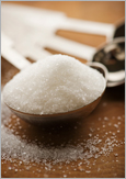 Photo of a measuring spoon full of sugar