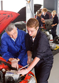 A photo of a student and a teacher repairing a car