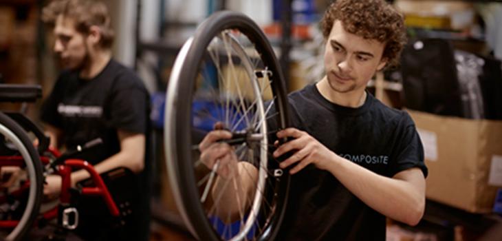 Photo d'un employé fabriquant une roue de fauteuil roulant. Photo prise dans l'atelier de Motion Composites.