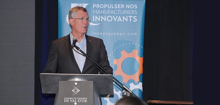Photo de monsieur Côté devant la bannière « Propulser nos manufacturiers innovants »