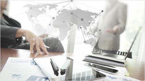 Photo d'employés devant une carte du monde virtuelle