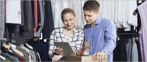 Photo d'employés d'un magasin de vêtements utilisant une tablette