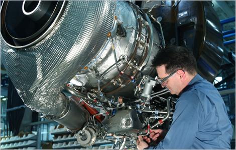 Photo of a technician repairing an aircraft engine.