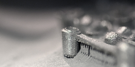Printing platform with object printed on 3d printer for metal and covered metallic powder. Photo credit: Shutterstock.