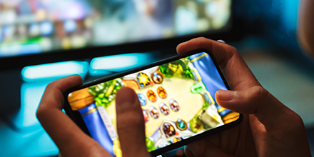 Photo of a person playing a video game with his cellphone