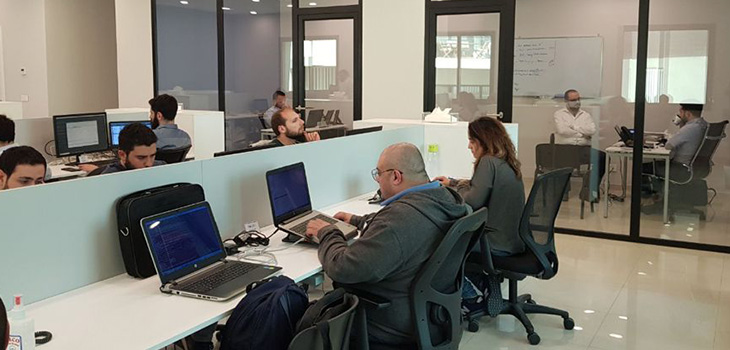 Photo of people working with laptops in an office