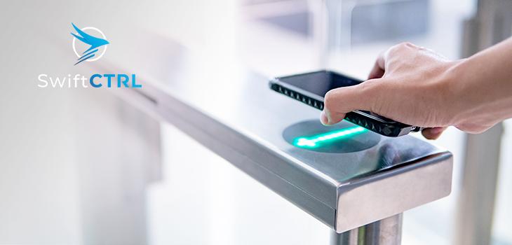 Photo d'une main masculine utilisant un téléphone intelligent pour ouvrir une machine à portail automatique dans un immeuble de bureaux