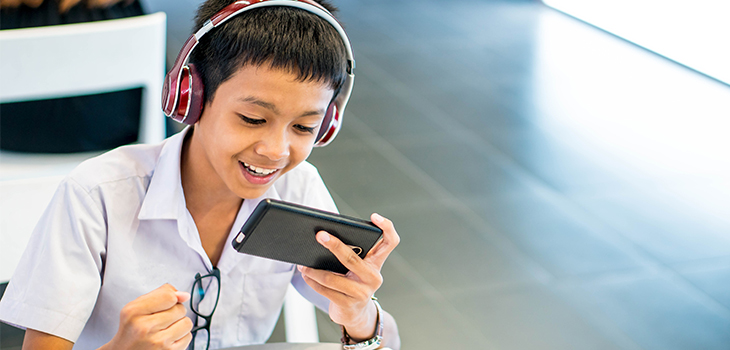 Photo of a boy with headphones watching a video on his cell phone