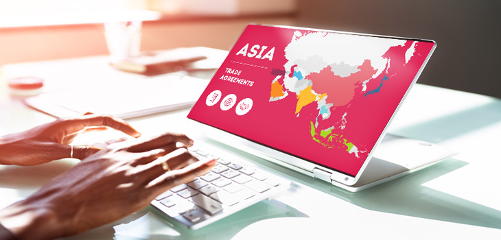 Photo des mains d'une personne touchant le clavier d'un ordinateur portable montrant une illustration d'une carte de l'Asie