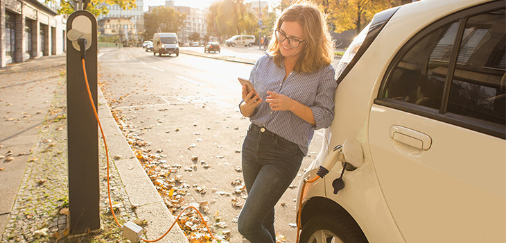 Young woman is standing near the electric car and looks at the smart phone. The rental car is charging at the charging station for electric vehicles.