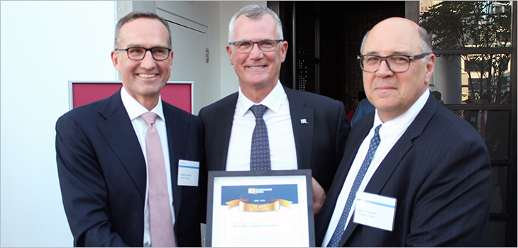 Photo of Mr. Côté awards a certificate commemorating 10 years of growth at Morgan Stanley to Rooney and Vesprini