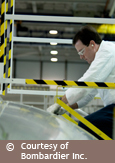 Photo of a man working on a Bombardier aircraft