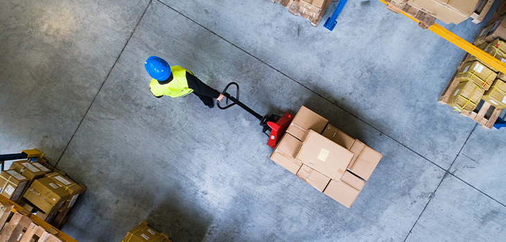Photo of a male warehouse worker pulling a pallet truck.