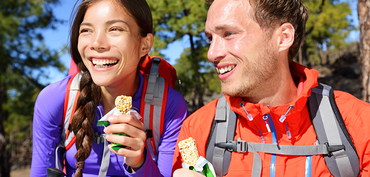 Photo of a couple eating a muesli bar while hiking.