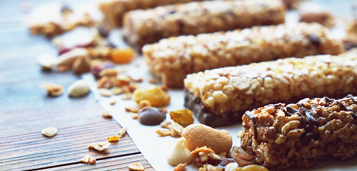 Photo of Healthy bars with nuts, seeds and dried fruits on the wooden table, with copy space.