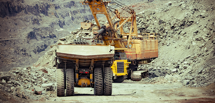 Photo of a heavy truck and an excavator in an open-pit iron mine