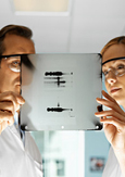 Photo of two biologists looking at an X-ray of DNA
