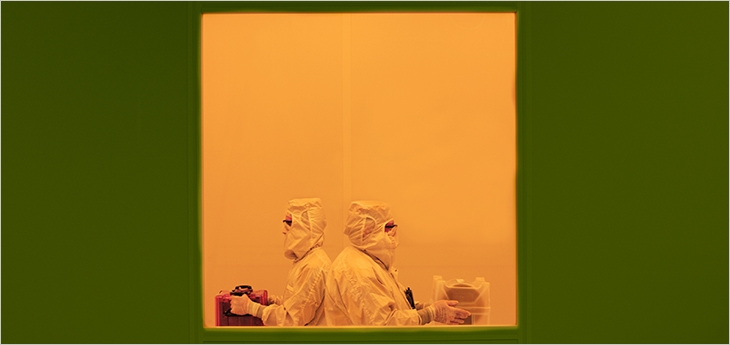 Photo of two technicians moving through the C2MI yellow room