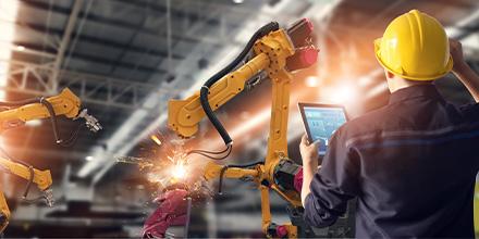 Photo d'un travailleur opérant des robots à l'aide d'une tablette numérique