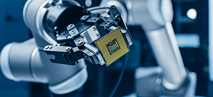 Photo of a robot holding a microchip in its gripper