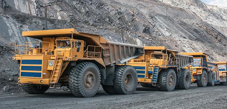 Photo de camions dans une mine à ciel ouvert