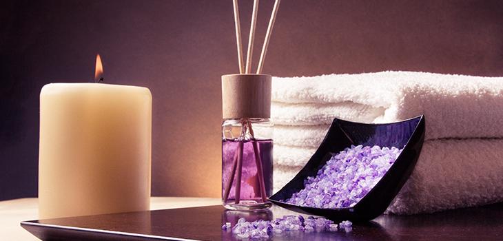 Photo d'une éprouvette contenant du parfum, d'un contenant de sel de mer, d'une chandelle et d'une serviette