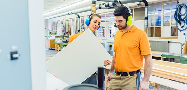 Photo de menuisiers inspectant une pièce de bois dans une usine