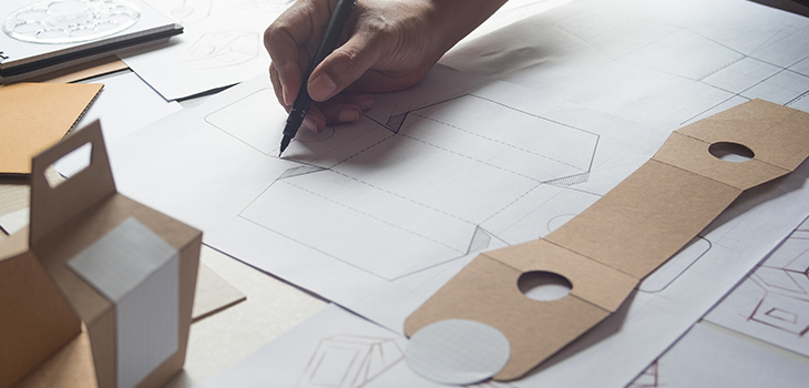 Photo d'une main dessinant un plan d'emballage flexible