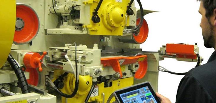 Photo d'un travailleur opérant une machine à l'aide d'une tablette numérique