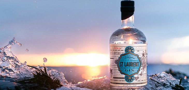 Photo d'une bouteille de gin de la Distillerie du St Laurent, avec le fleuve en arrière-plan