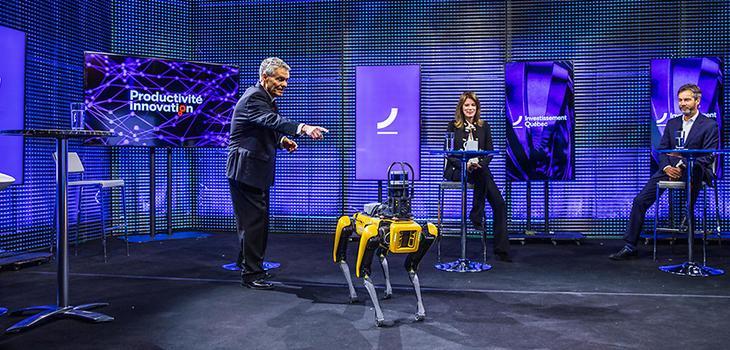 Photo de Paul Houde, Sylvie Pinsonnault et Guy LeBlanc sur une scène avec un robot lors du Forum Productivité Innovation