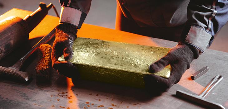 Photo d'un travailleur déposant un lingot d'or sur un établi